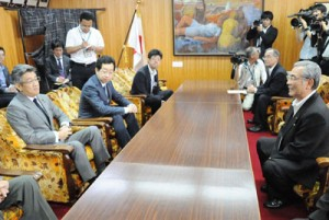 朝山市長(手前右)と会談する武田副大臣(同左)=21日、奄美市役所