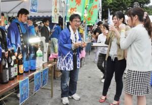 杜氏の説明を聞きながら黒糖焼酎を試飲する来場者=9日、奄美市名瀬