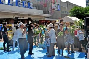 テッポウユリの切り花配布に喜ぶ来場者ら=8日、尼崎市の阪神尼崎駅前広場