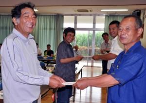 共催者から記念品を受け取る新規就農者(左列)=5日、和泊町のえらぶ長浜館