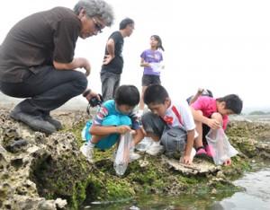 ヤコウガイの稚貝を放流する天城小の児童ら=11日、天城町