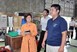 沖永良部酒造の徳田英輔取締役(右)の説明を聞く上野氏(左)=11日、和泊町