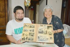 思い出の写真を手に姉とブラジルを思う泉さん(右)=21日、宇検村芦検