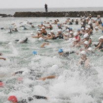 一斉に水しぶきを上げてスタートを切る選手ら=29日、天城町ヨナマビーチ