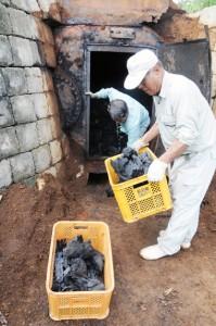 完成した木炭を窯から取り出す作業員=26日、和泊町谷山