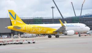 奄美路線の就航を控えたバニラ・エアの機材。背後は2014年度末の完成をめどに建設中のLCC専用ターミナル=28日、成田空港