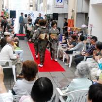 多くの観光客でにぎわった大島紬ファッションショー=10日、奄美市名瀬