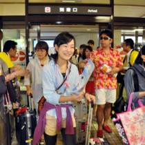 あまみシマ博のガイドブックを手にする到着客=18日、奄美空港