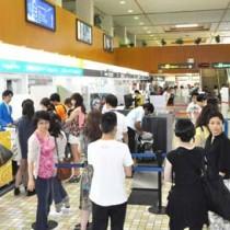 利用客で混雑するバニラ・エアの受付カウンター=10日正午前、奄美空港