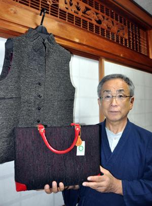 裂き織りの生地を使った製品を手にする元社長=9日、奄美市名瀬