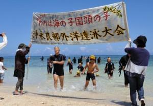 最後まで泳ぎ切り、笑顔でゴールする子どもたち=20日、和泊町のワンジョビーチ