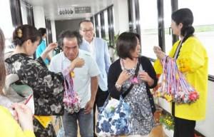 黒糖のレイで初便の乗客を出迎える奄美大島観光協会のメンバーら=1日、奄美空港