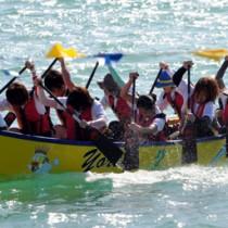 太陽の日を浴びてきらめく海面を疾走する、郡体競技出場カヌー=12日、与論町茶花海岸特設ステージ