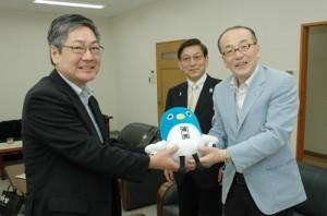 成田市の観光キャラクターのぬいぐるみを届けた小泉市長(右)とバニラ・エアの石井社長〈中央)=2日、南海日日新聞社