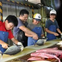 シマ博でマグロのさばき方を教わる子どもたち=27日、奄美市名瀬大熊町の宝勢丸鰹漁業生産組合