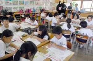 コクトくんと対面し、一生懸命に暑中見舞いを書く児童たち=17日、名瀬小学校