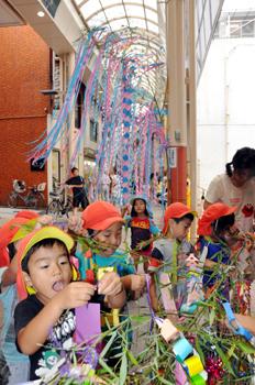 願い事を書いた短冊をササに結び付ける子どもたち=30日、奄美市名瀬のティダモール中央通り