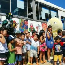 ラッピングバスを背景に琉神マブヤーと記念撮影する子どもたち=27日、県奄美パーク