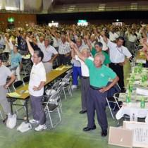 頑張ろう三唱で増産へ向け意気込む参加者=5日、和泊町民体育館