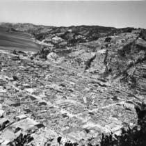 おがみ山から撮影したとみられる名瀬の街。裏書きには「米軍が来島、当時の名瀬市。S21、22年ごろ」。山の頂まで開墾されていた状況が分かる