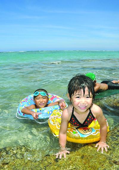 波打ち際で海水浴を楽しむ子どもたち=13日午前11時20分、奄美市の大浜海浜公園
