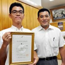 日商簿記1級の合格証書を手にする中君(左)と長倉教諭=30日、奄美高校