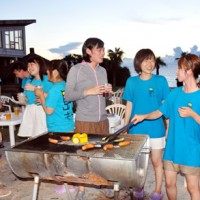 バーベキューで交流を広げる島キャンの参加学生=25日、奄美市名瀬の大浜海浜公園