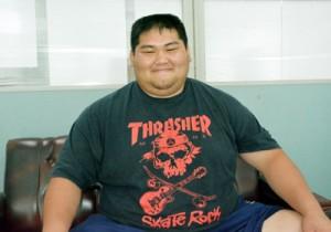 「応援よろしくお願いします」と笑顔を見せる坂元主将=22日、南海日日新聞社