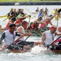 奄美まつりの名物・舟こぎ競争。力強いかいさばきで波を切る選手たち=16日、奄美市名瀬
