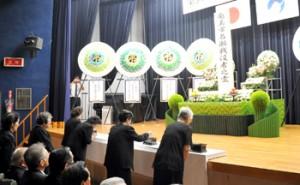 恒久平和への願いを込めて合掌する参列者ら=15日、奄美市名瀬公民館