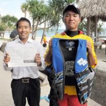 ライフジャケットの着用を呼び掛ける西さん(右)とチラシを手にする佐野代表=20日、奄美市笠利町用安