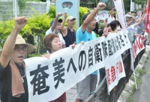 部隊配備反対を訴えこぶしを突き上げる反対集会の参加者
