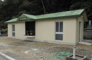 落成した瀬武集落の共同納骨堂(写真上)と住民、出身者ら約30人が出席した完成祝賀会=2日、瀬戸内町