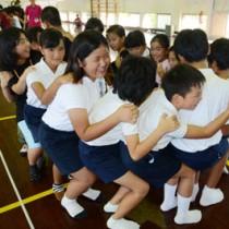 ゲームで交流する田皆子ども会と神戸市の子どもたち=22日、知名町