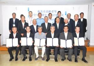 「高齢者見守り活動」を協定した朝山市長(前列中央)と市内11事業者=12日、奄美市役所