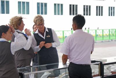 「ザ・ワールド」の女性乗務員に商品の説明をする奄美サウスシー&マベパールの社員