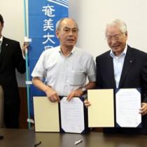 調印式で高齢者の見守り活動での連携を確認する築理事長と川島町長(右から)=21日、喜界町役場