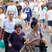 ちょうちんを掲げて祖先を送る人々=10日、奄美市名瀬の永田墓地