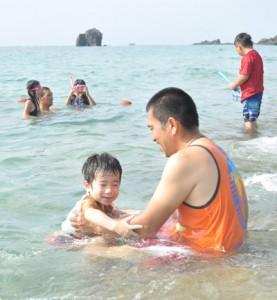 夏休み最終日を楽しむ親子連れ=31日、奄美市名瀬の大浜海浜公園