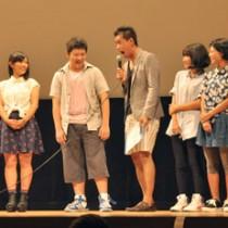 石田さん(中央)とやり取りする出演者の中高生5人=16日、奄美文化センター