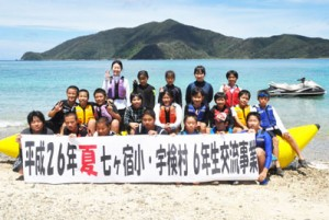 宇検村の児童ら記念撮影する七ヶ宿小の児童ら=18日、宇検村タエン浜海水浴場