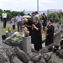 慰霊碑に献花して犠牲者の冥福を祈る参加者ら=23日、徳之島町