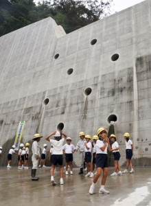 砂防ダム本体を間近で見学する大勝小の5、6年生児童=17日、龍郷町