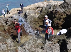 岩に海水をたたきつける汐干し体験をする児童ら=4日、和泊町国頭の海岸