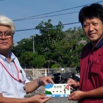 平安町長(左)から知名町ご当地ナンバープレートの交付を受ける田原さん=1日、知名町役場前