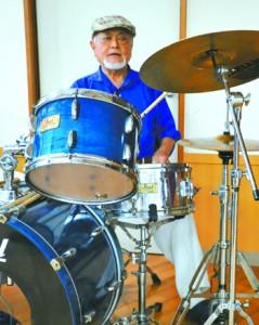 玉里地区の敬老会で華麗なドラムソロを披露する坂井さん=14日、龍郷町