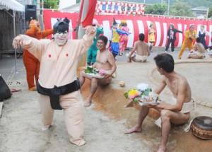 仮装した女性たちがユーモラスな踊りで会場を沸かせた名音集落の豊年祭=28日、大和村