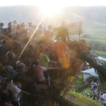 集落と田袋を見下ろす山の中腹で「ショチョガマ」を揺さぶる男衆=2日午前6時半ごろ、龍郷町秋名