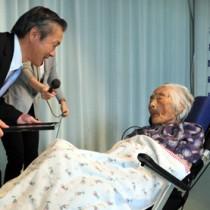 本支庁長から祝福の言葉をかけられる県内最高齢の田島ナビさん=11日、喜界町