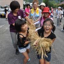 地域の子どもたちと一緒に綱引きを体験するツアー参加者=8日、奄美市住用町西仲間